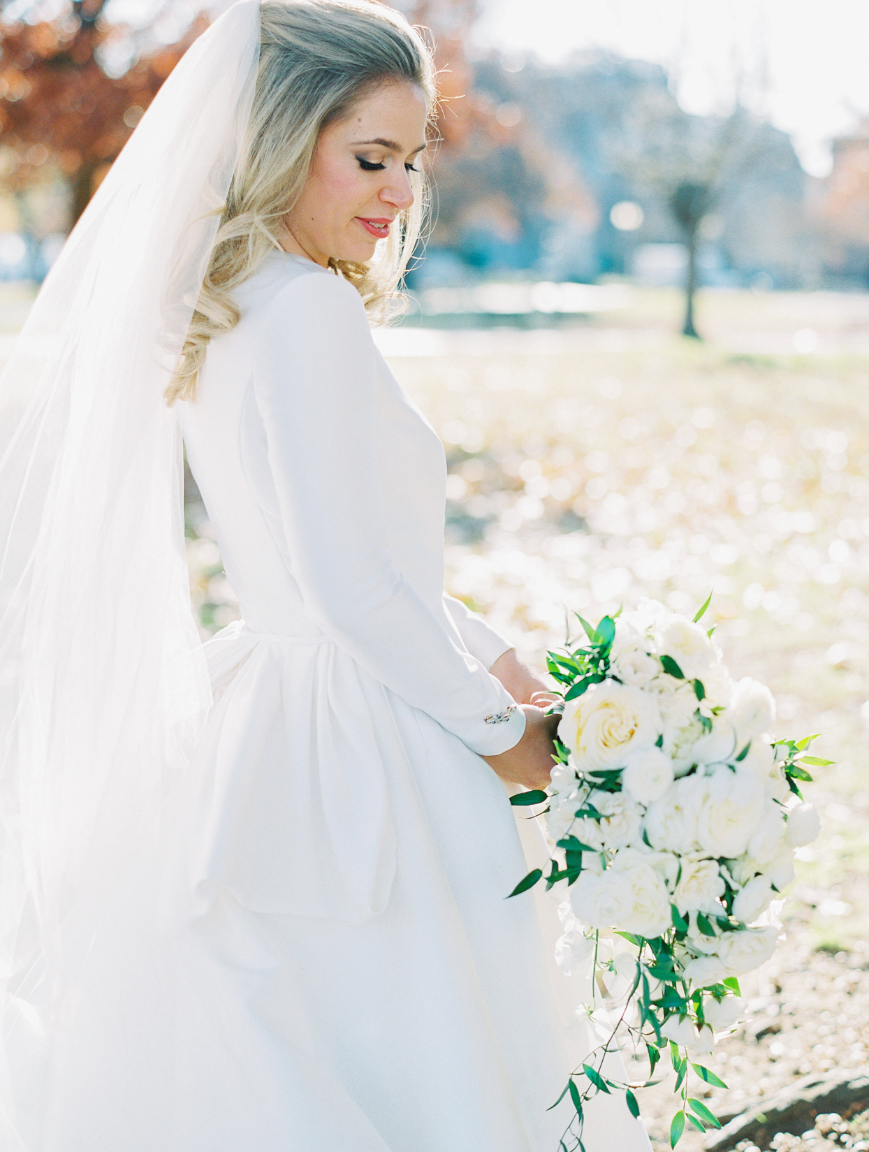 bride in long sleeve dress holding white bouquet