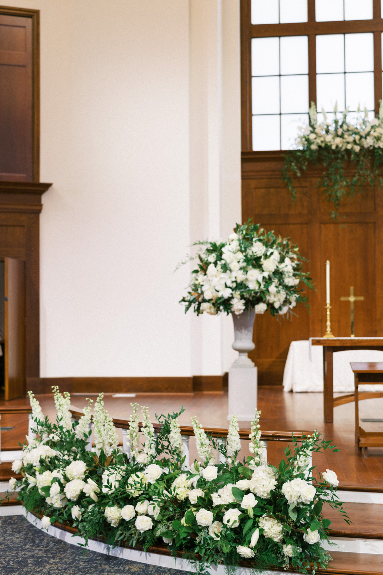 white florals decorating church for indoor wedding