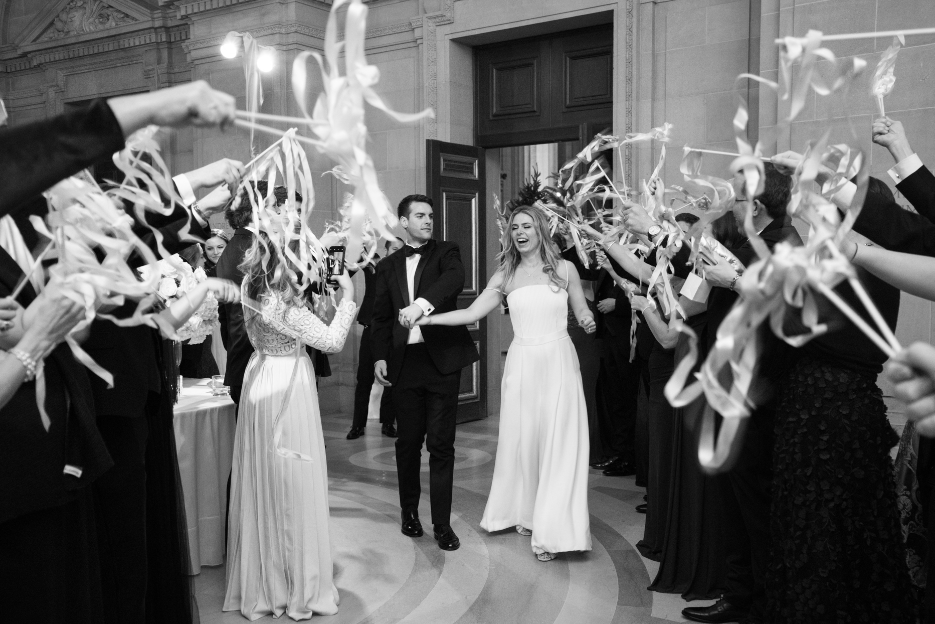 couple exiting wedding reception while guests hold streamers