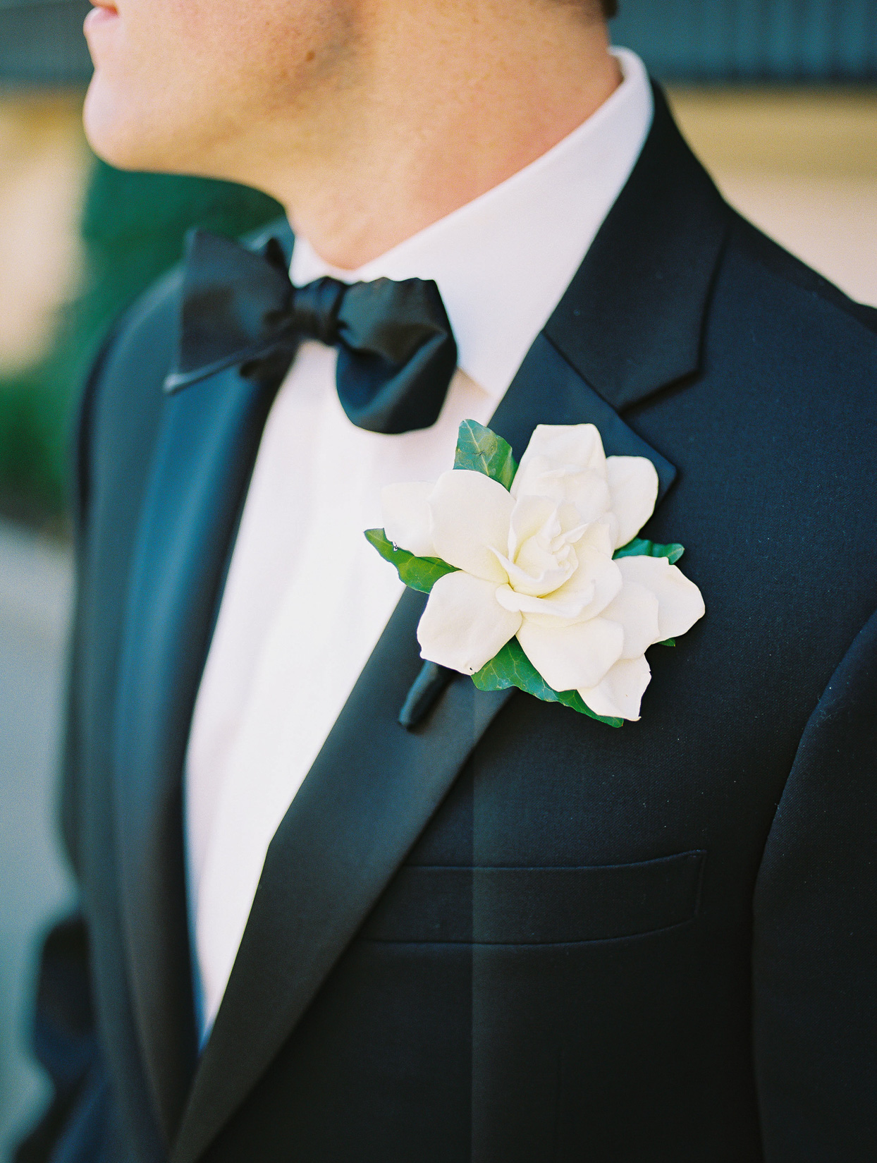 white floral boutonniere on groom's black tux