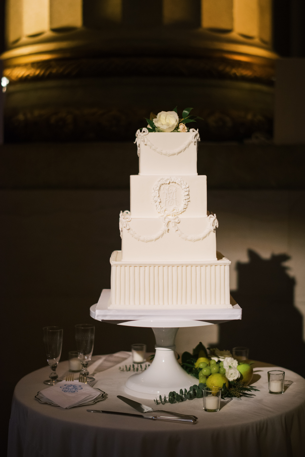 four-tiered white wedding cake on round table