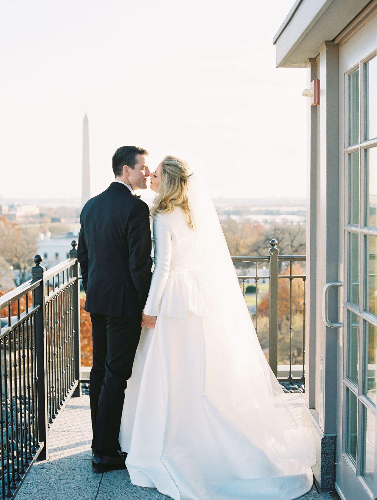 couple kiss on balcony with D.C. washington monument view