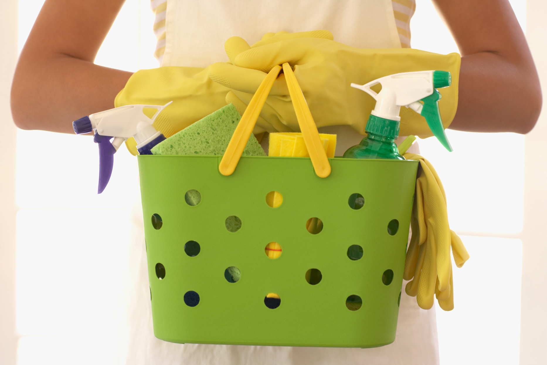 woman carrying green basket of cleaning supplies