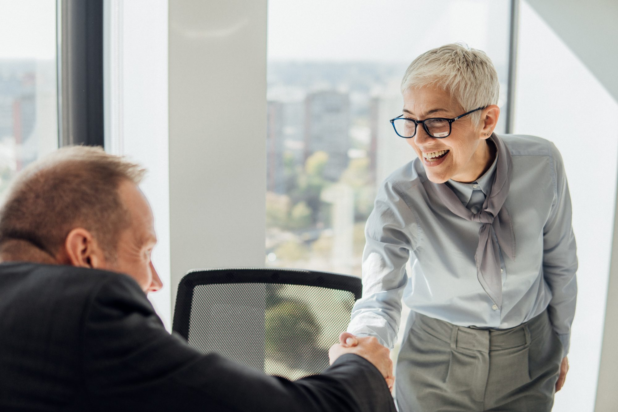 Smiling woman shaking hands with a coworker