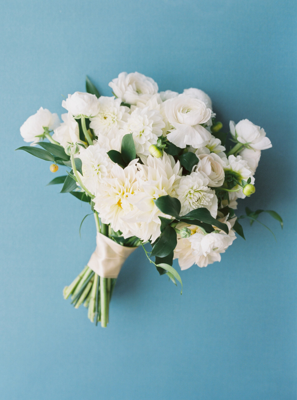 bridal bouquet comprised of white dahlias and ranunculus blossoms