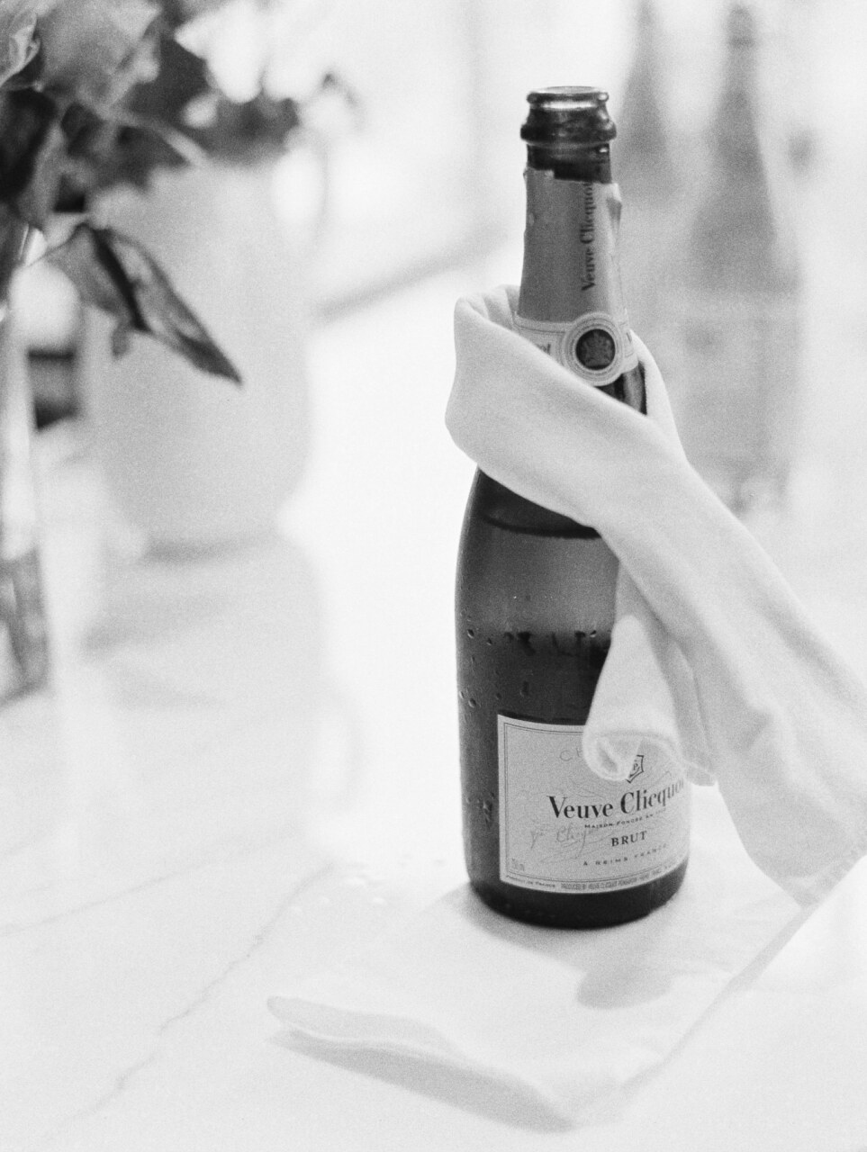 cloth napkin wrapped around bottle of champagne