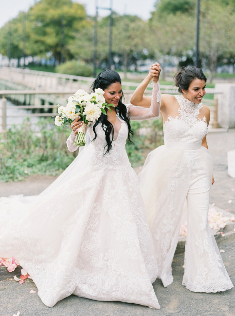 brides lifting their held hands during wedding ceremony recessional
