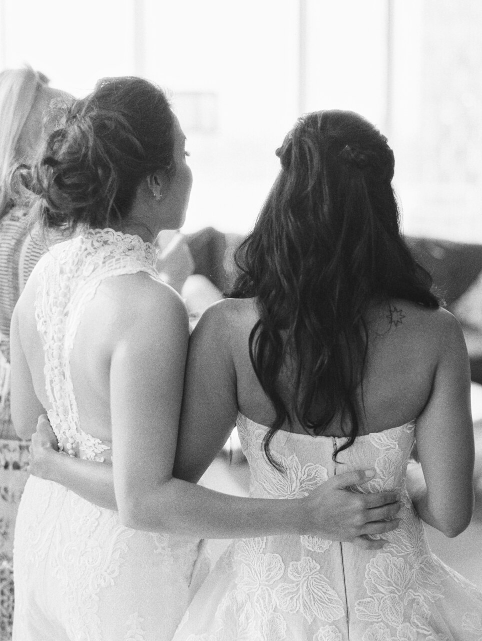 backside of brides with arms around one another