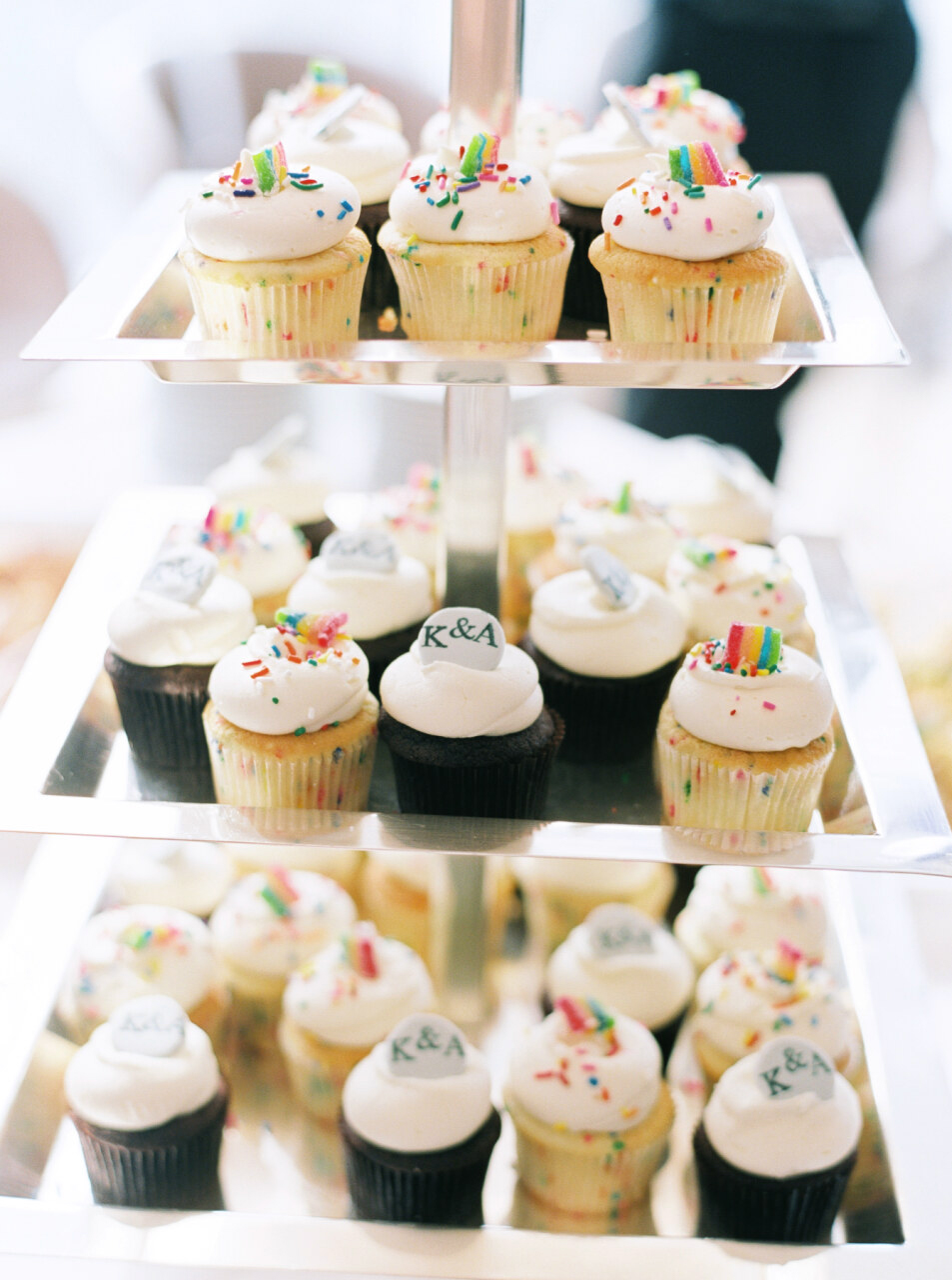 wedding cupcakes with alternating toppers of rainbows and embossed initials