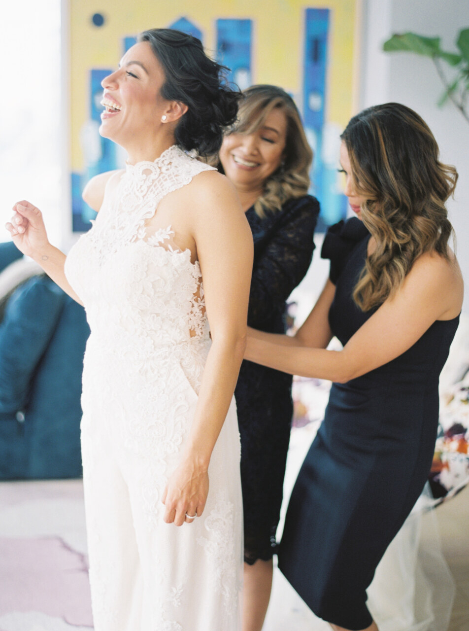 mother and sister zipping brides jumpsuit