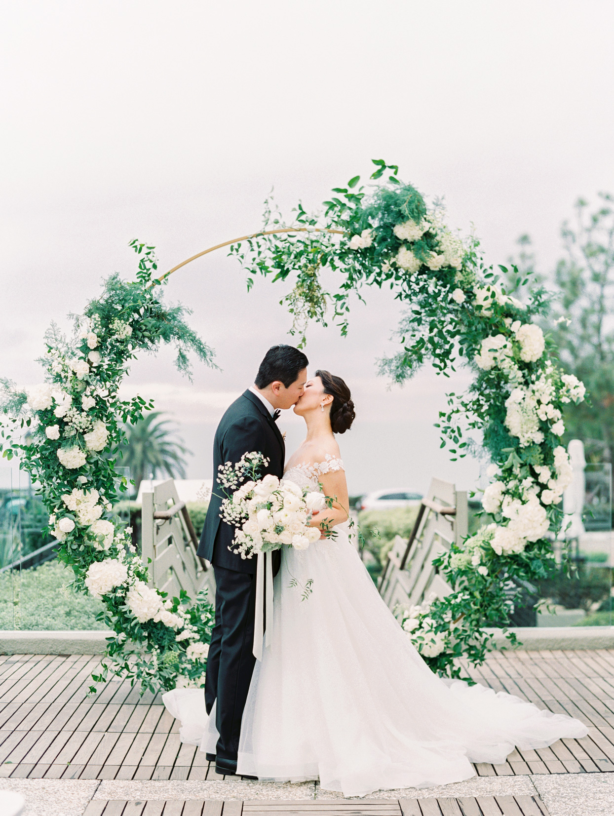 wedding couple kiss in front of circular floral arch