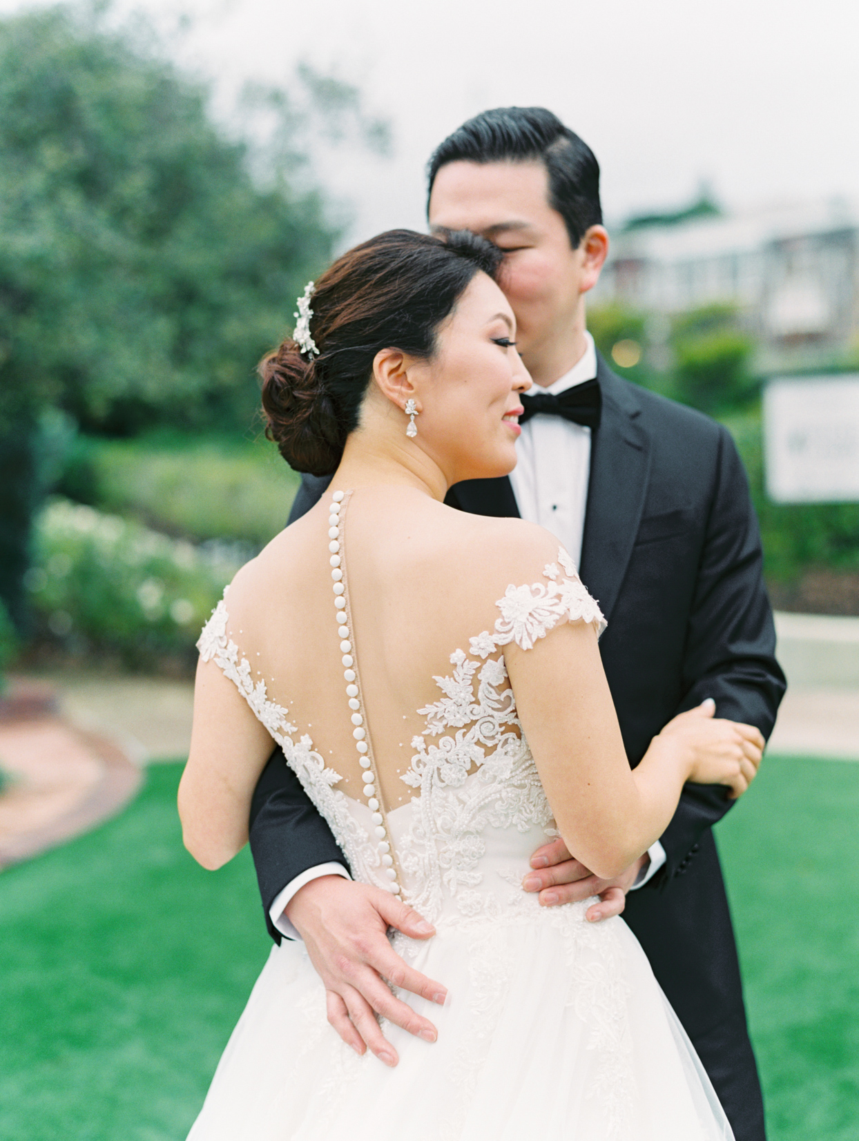 couple posing with bride's white buttoned wedding dress displayed