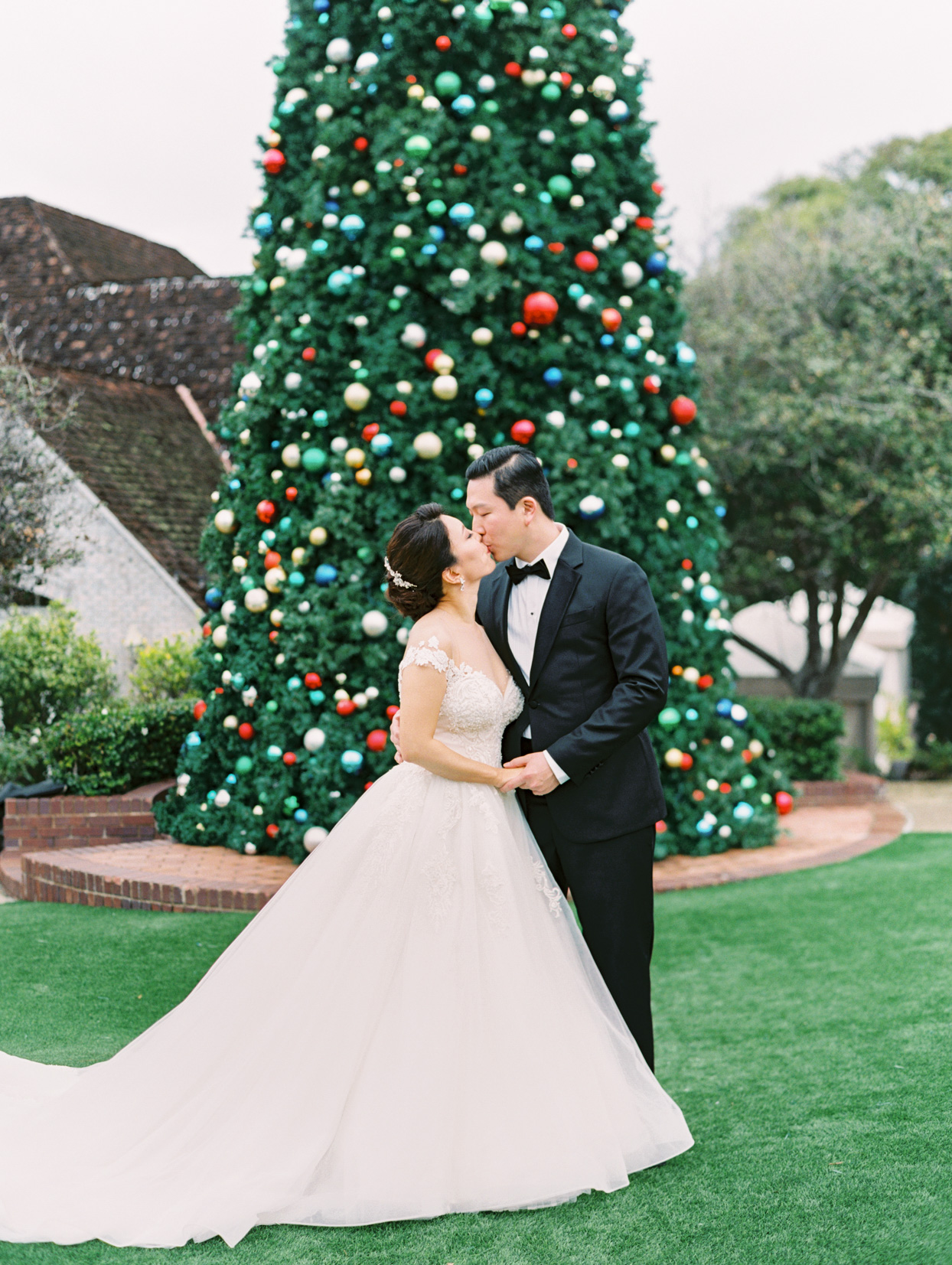 wedding couple kiss in front of giant christmas tree