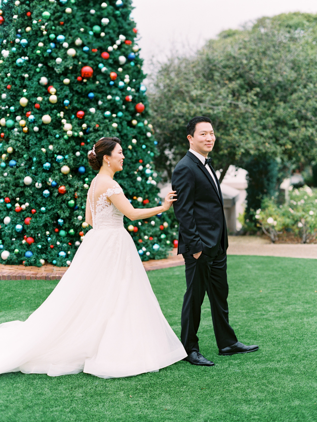 bride tapping groom's shoulder for first look in front of christmas tree