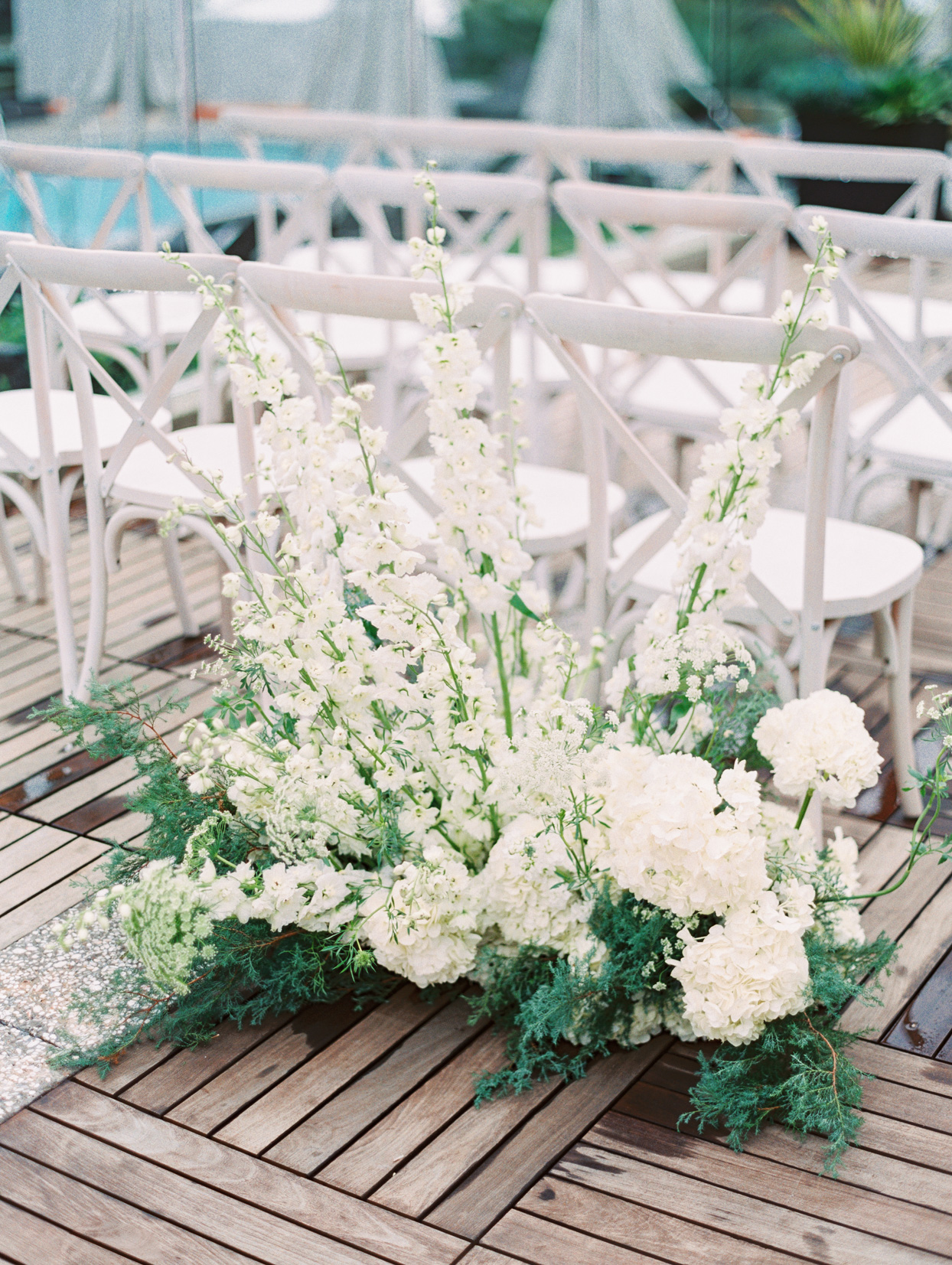 white floral arrangements at base of ceremony chairs