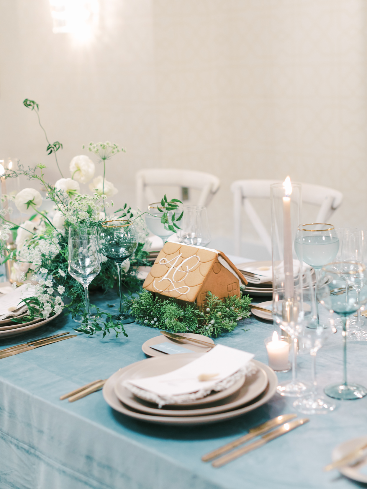 elegant blue table setting with decorative gingerbread houses and candles