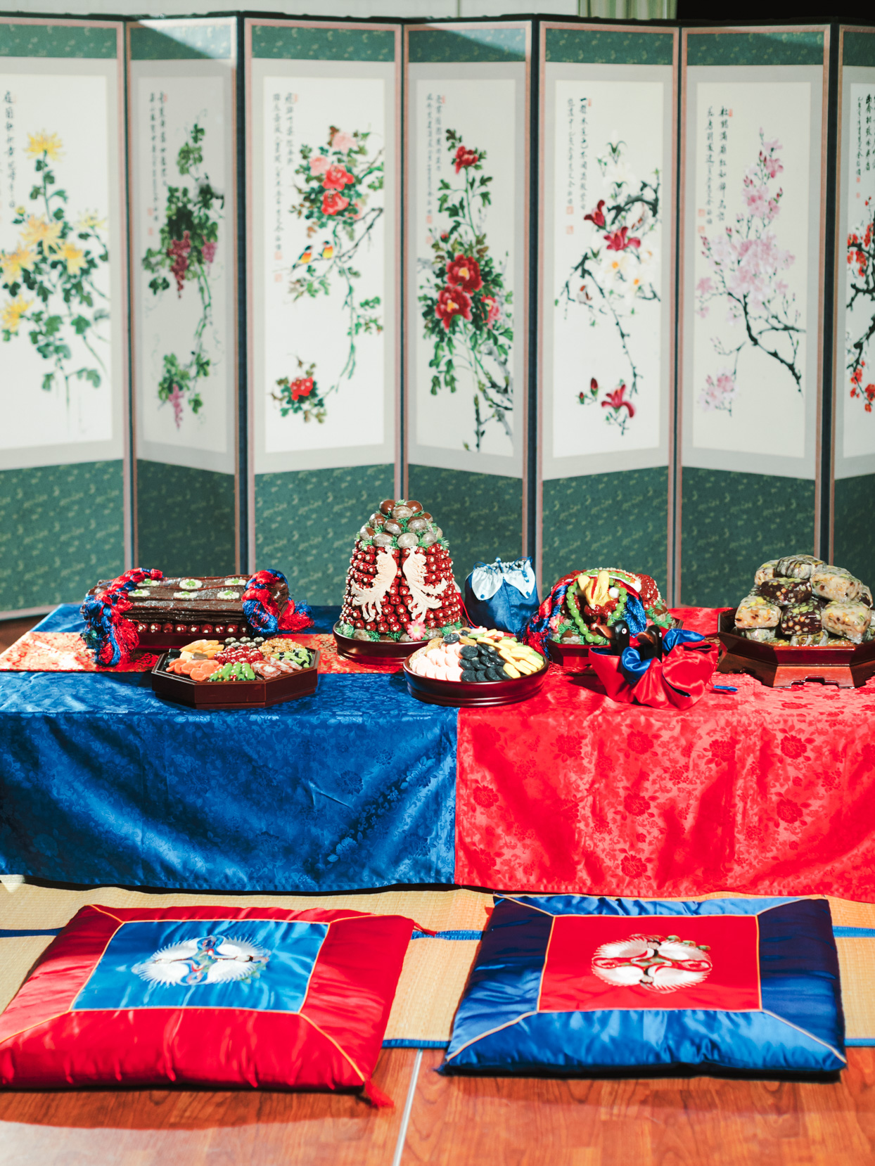 wedding paebaek ceremony with red and blue table and cushions
