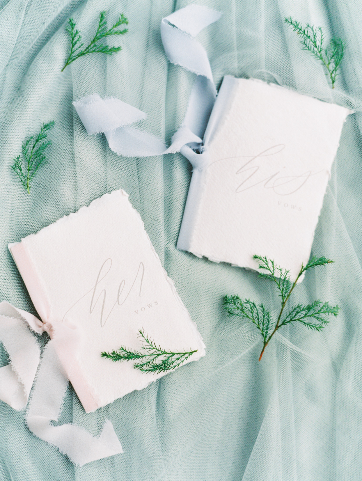 vow books with torn edges and festive greenery