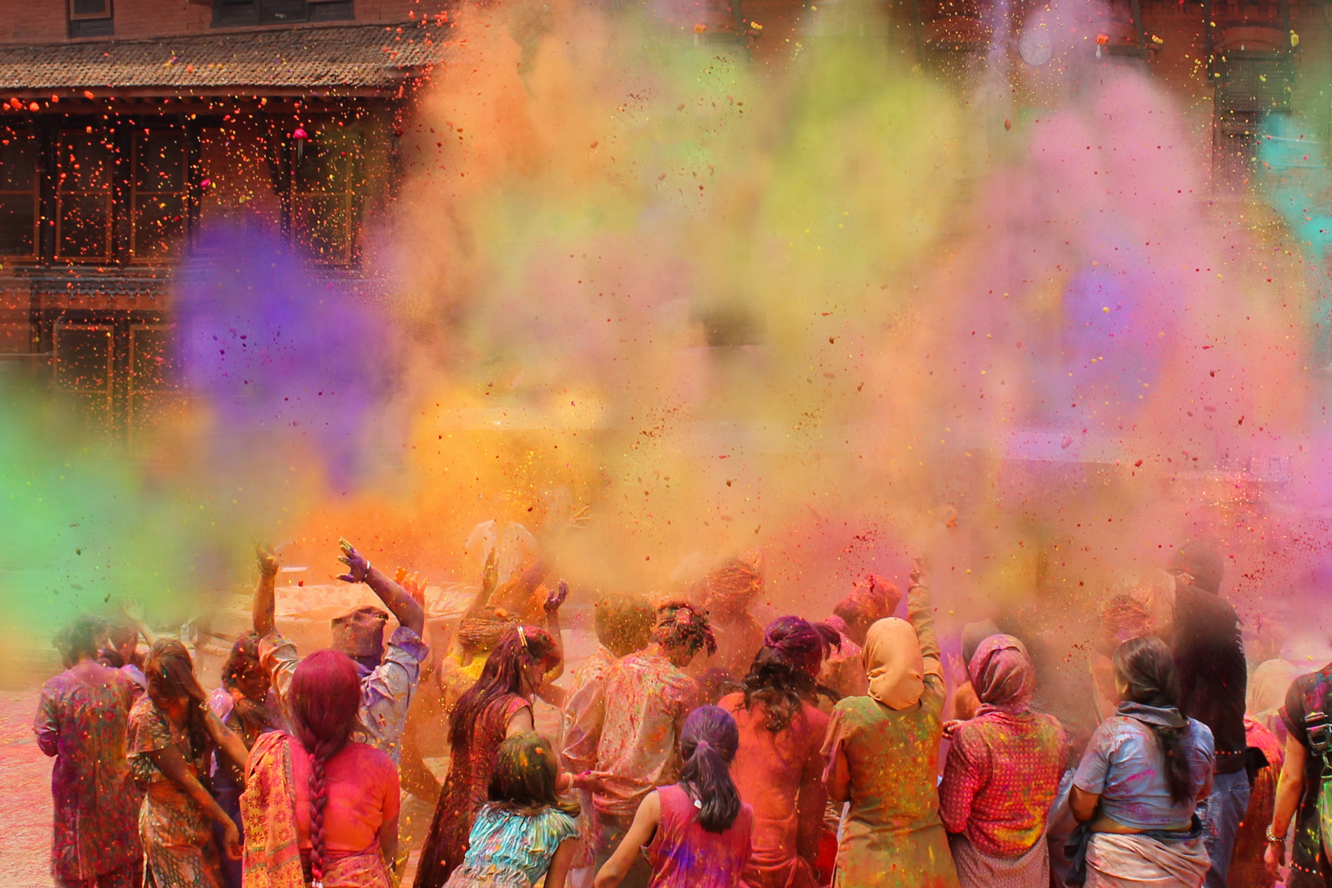 group of people celebrating holi with colorful powder