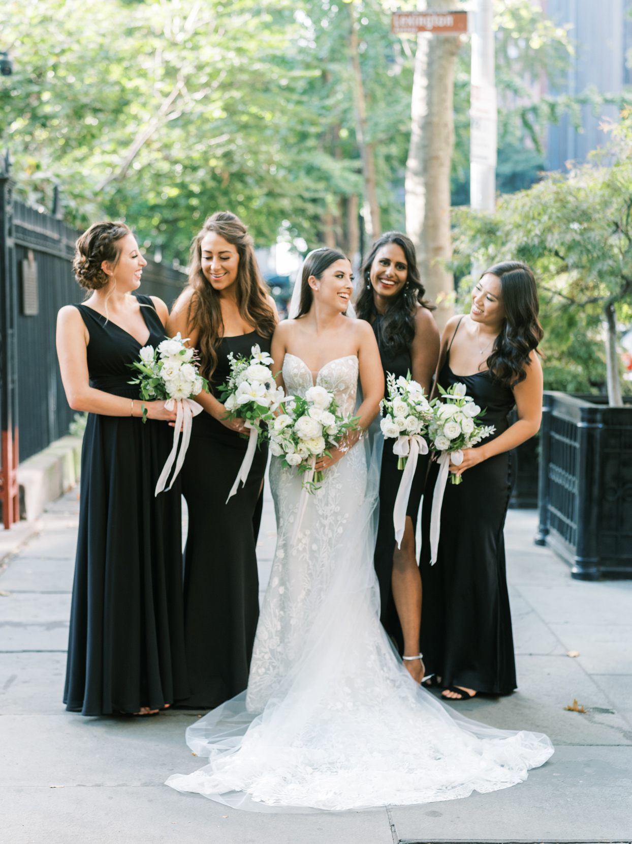 bridesmaids in black with bride posing on lexington ave