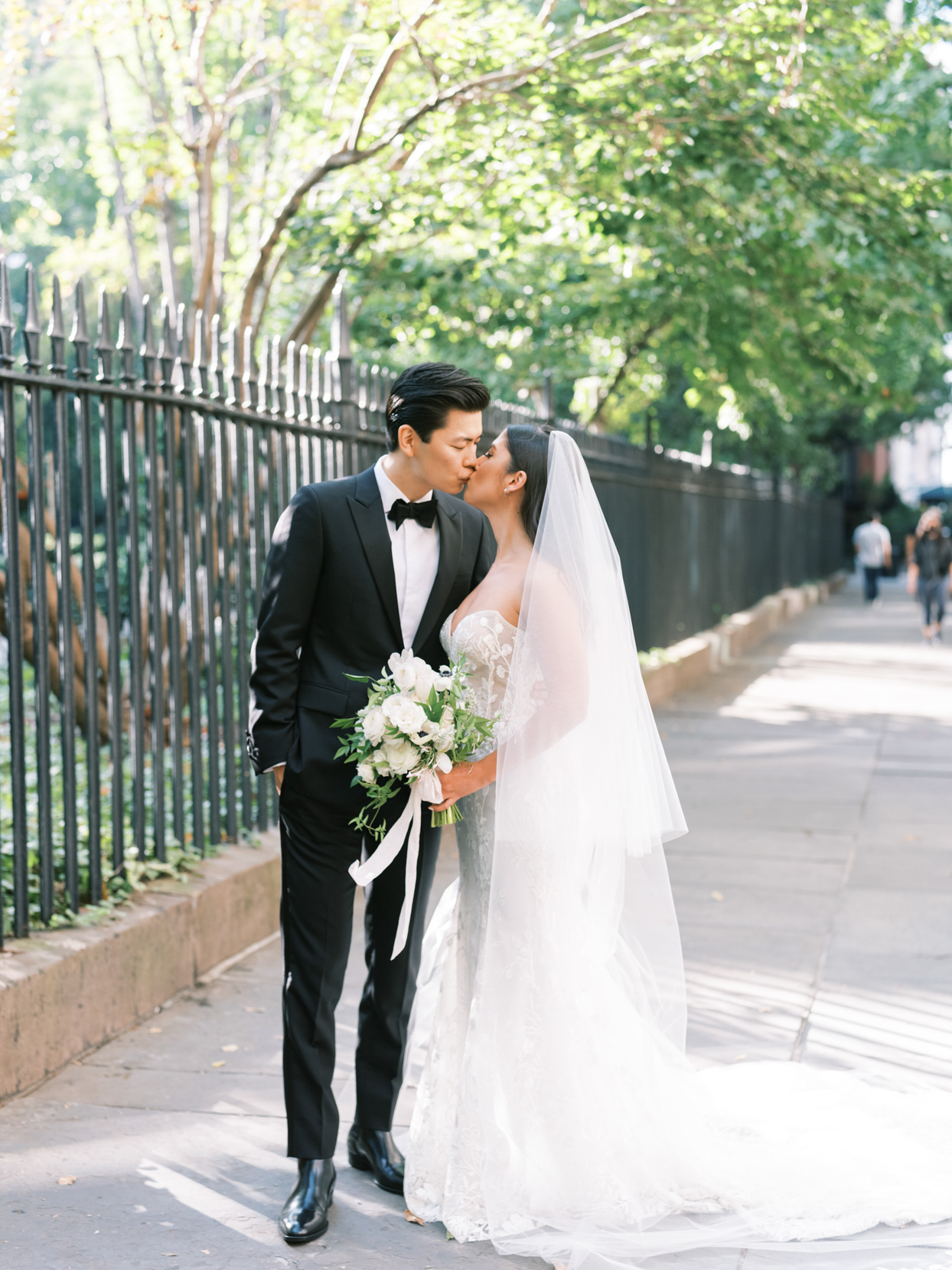 bride and groom kiss by edge of central park