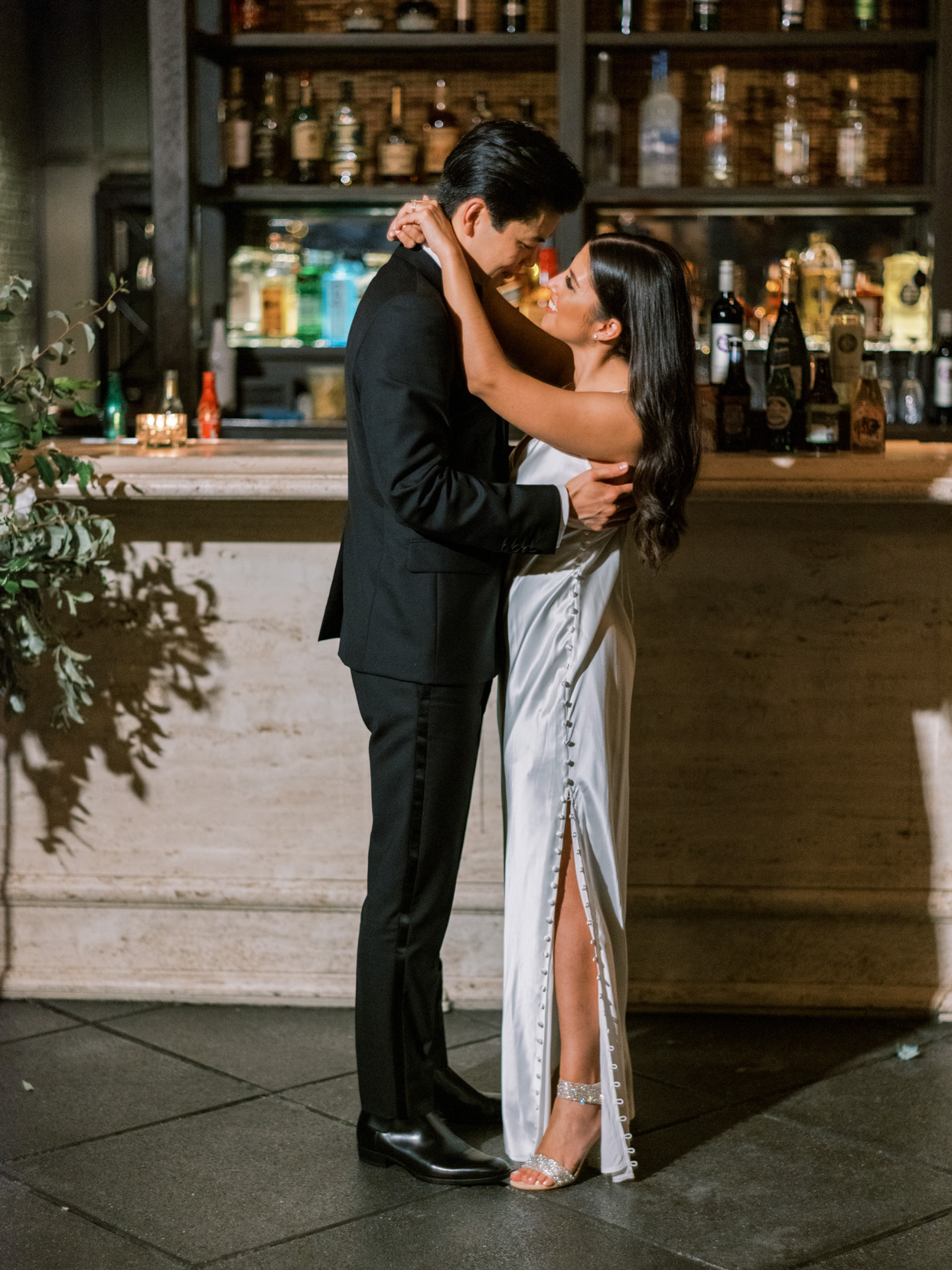 bride and groom embracing in front of bar after bride's outfit change