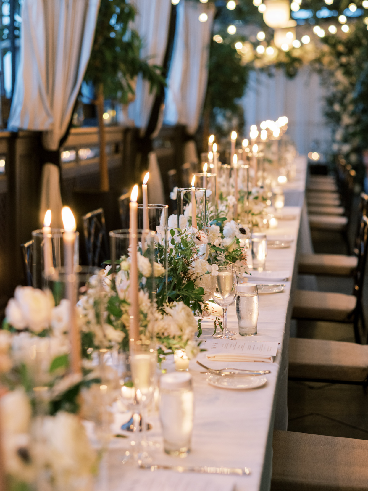 long reception tables lit with candles and floral decor
