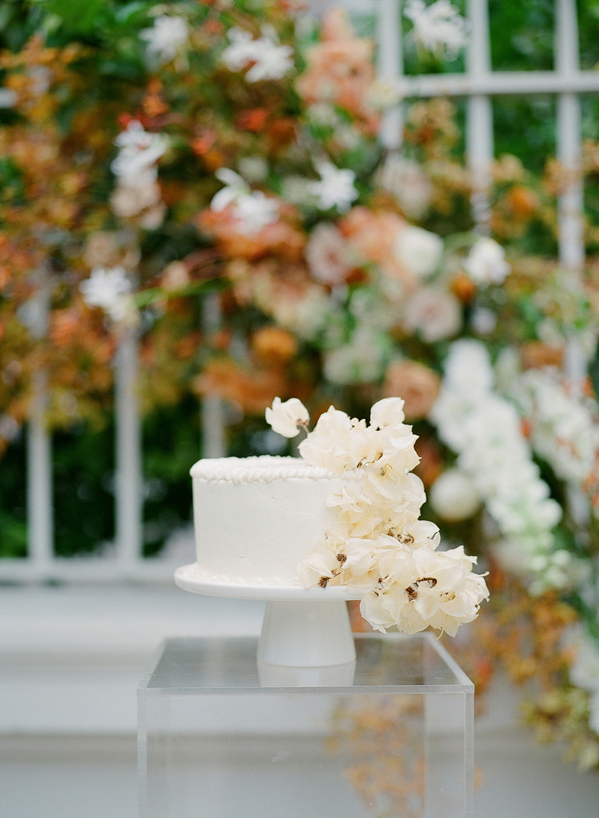 single layer wedding cake with waterfall of cream colored flowers