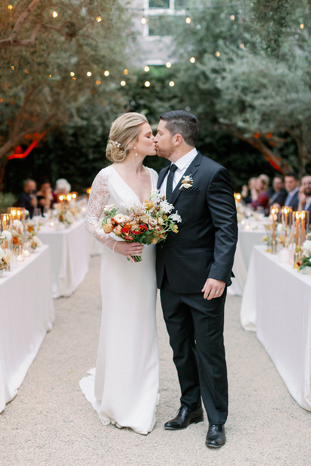 wedding couple kissing between rows of tables for outdoor ceremony