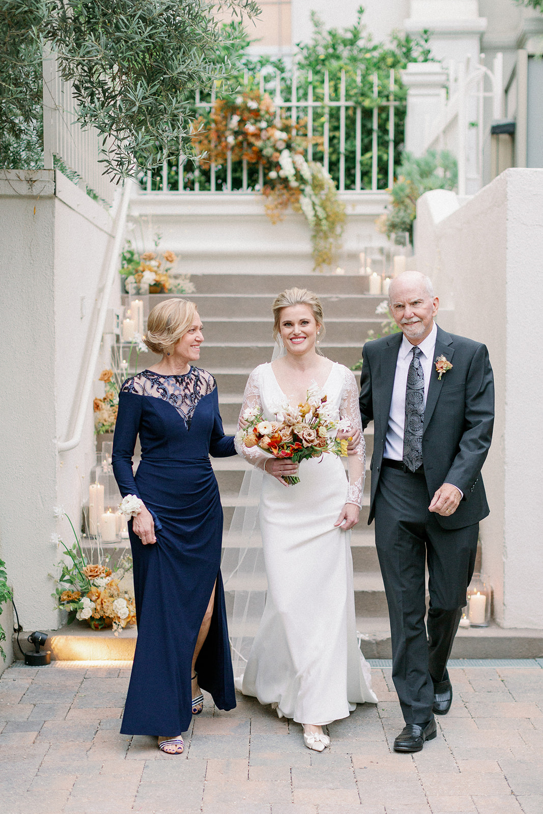 bride entering wedding with mother and father