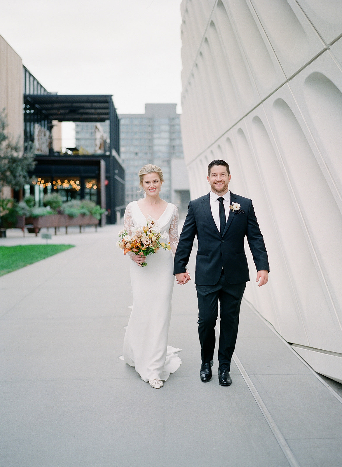 bride and groom holding hands walking by modern architecture