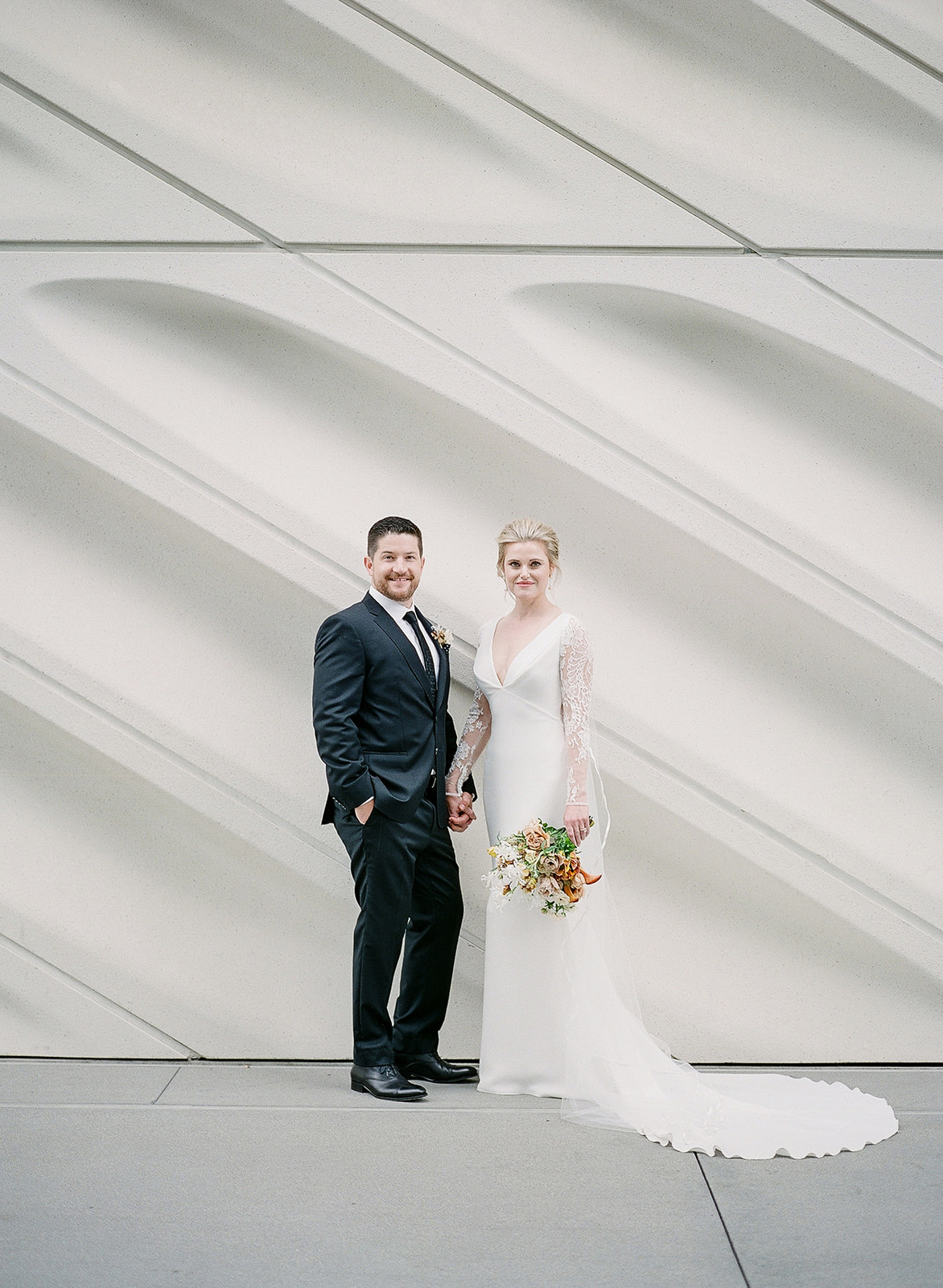 wedding portrait in front of modern white building