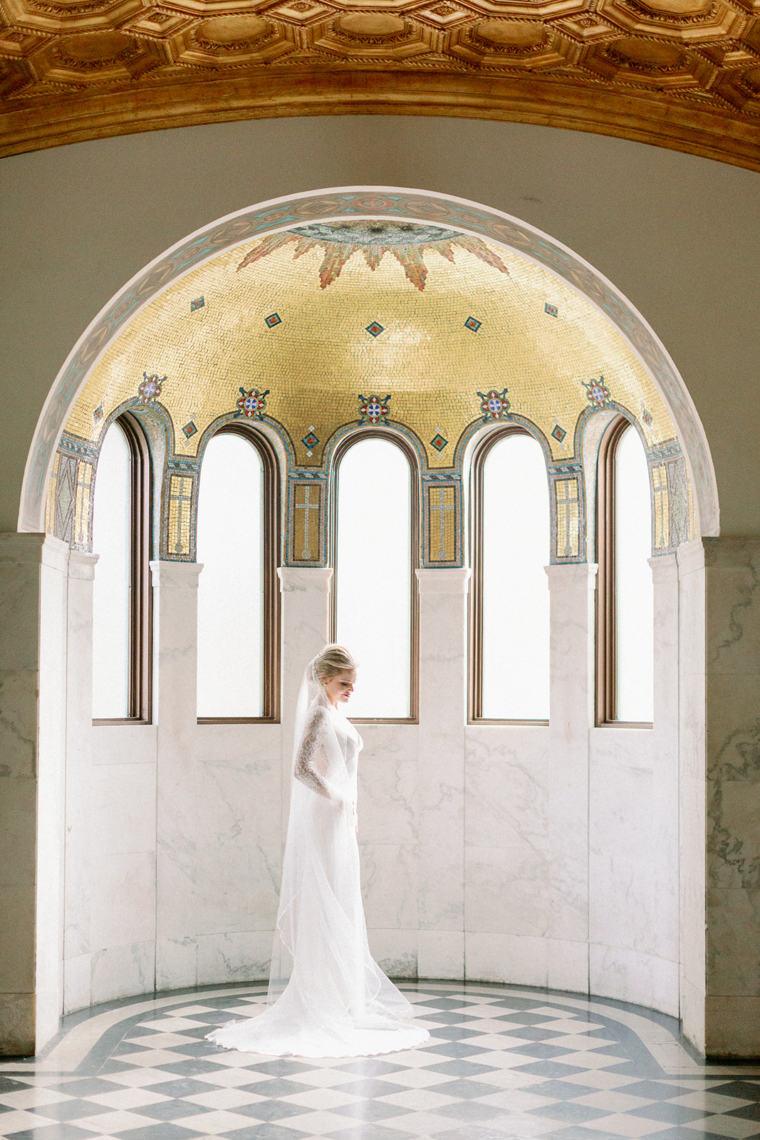 bride standing in elegant cathedral arch