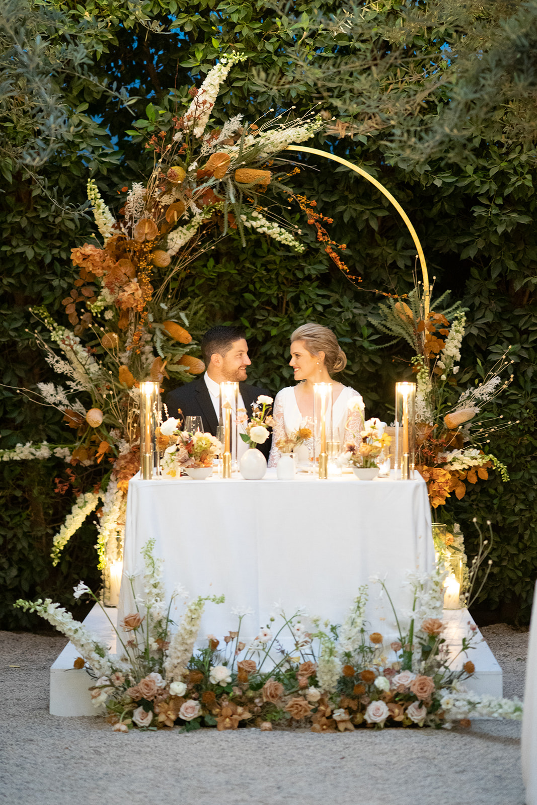 couple sitting at sweet heart table under Ikebana-Style Floral arch