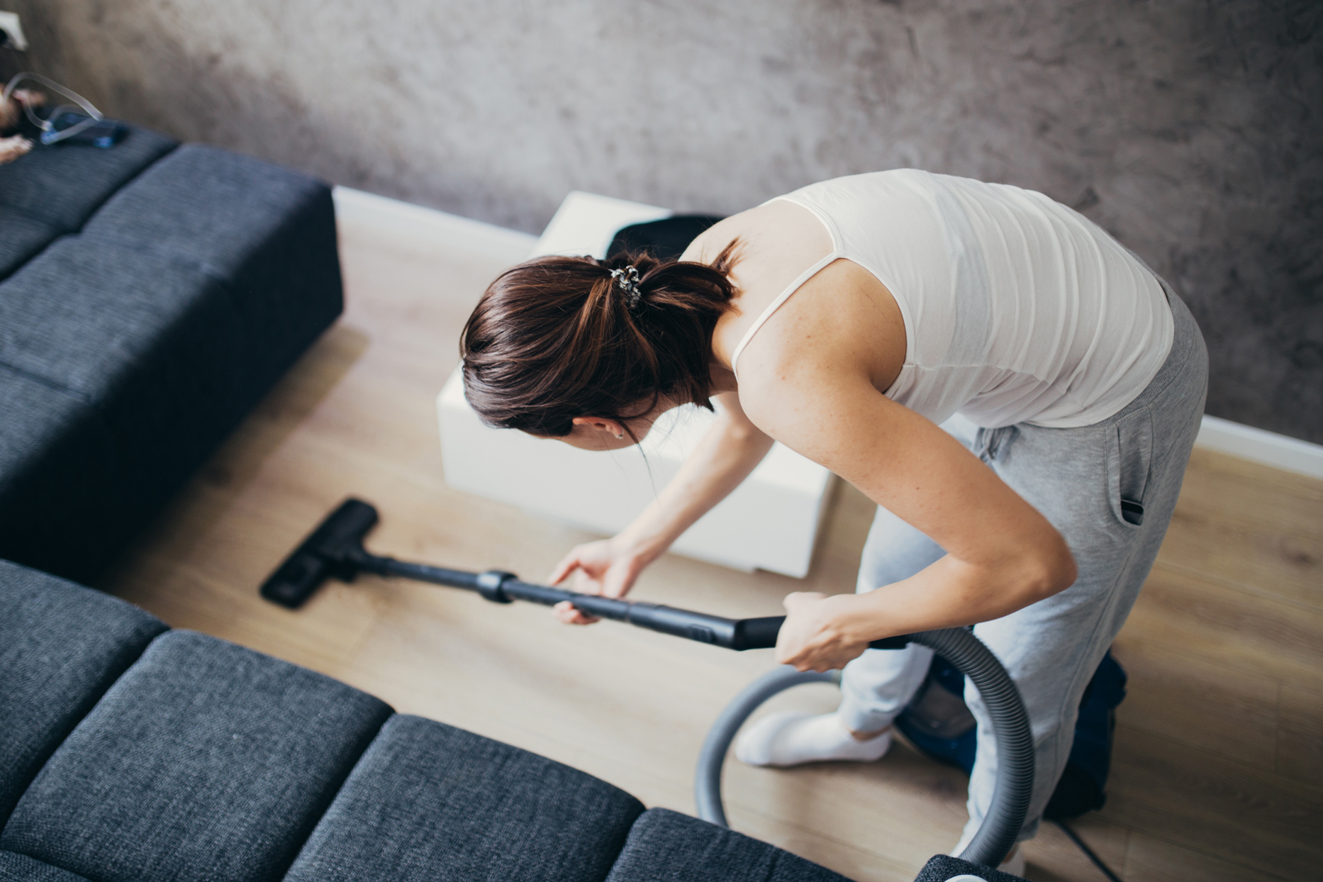 person vacuuming hard wood floor next to couch