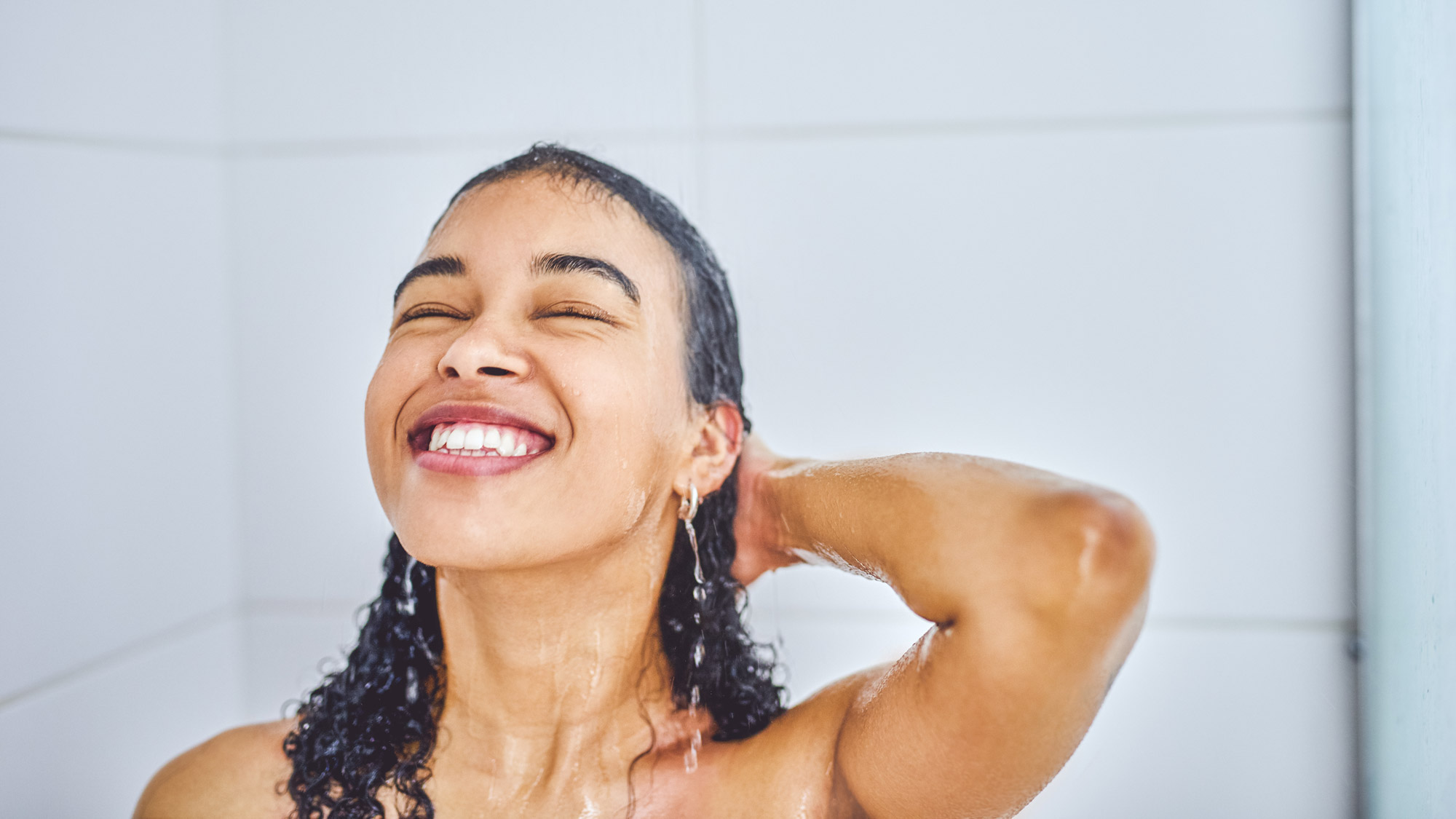 smiling woman in shower with wet hair