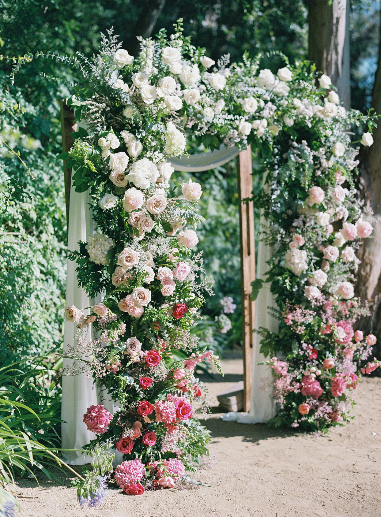 large white and pink floral wedding arch