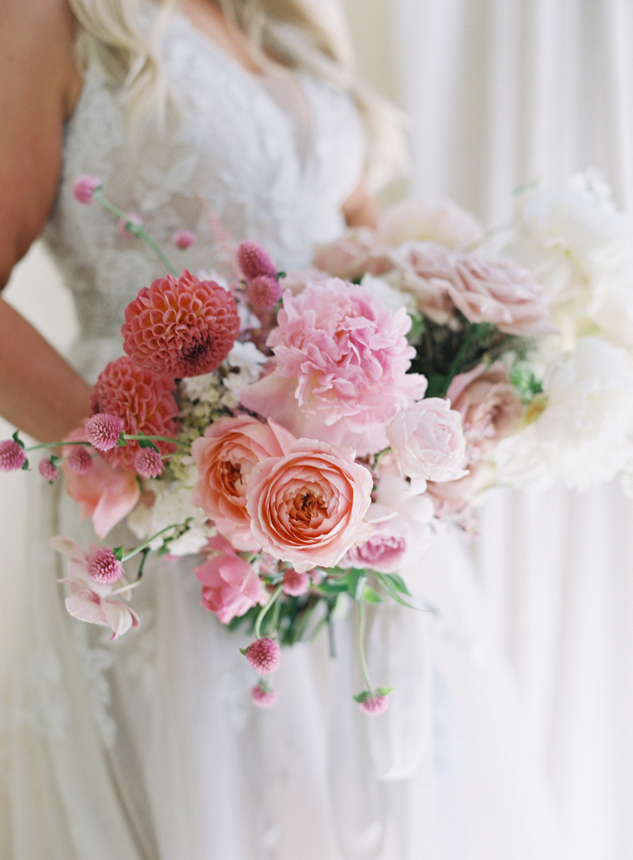 bride holding pink floral wedding bouquet