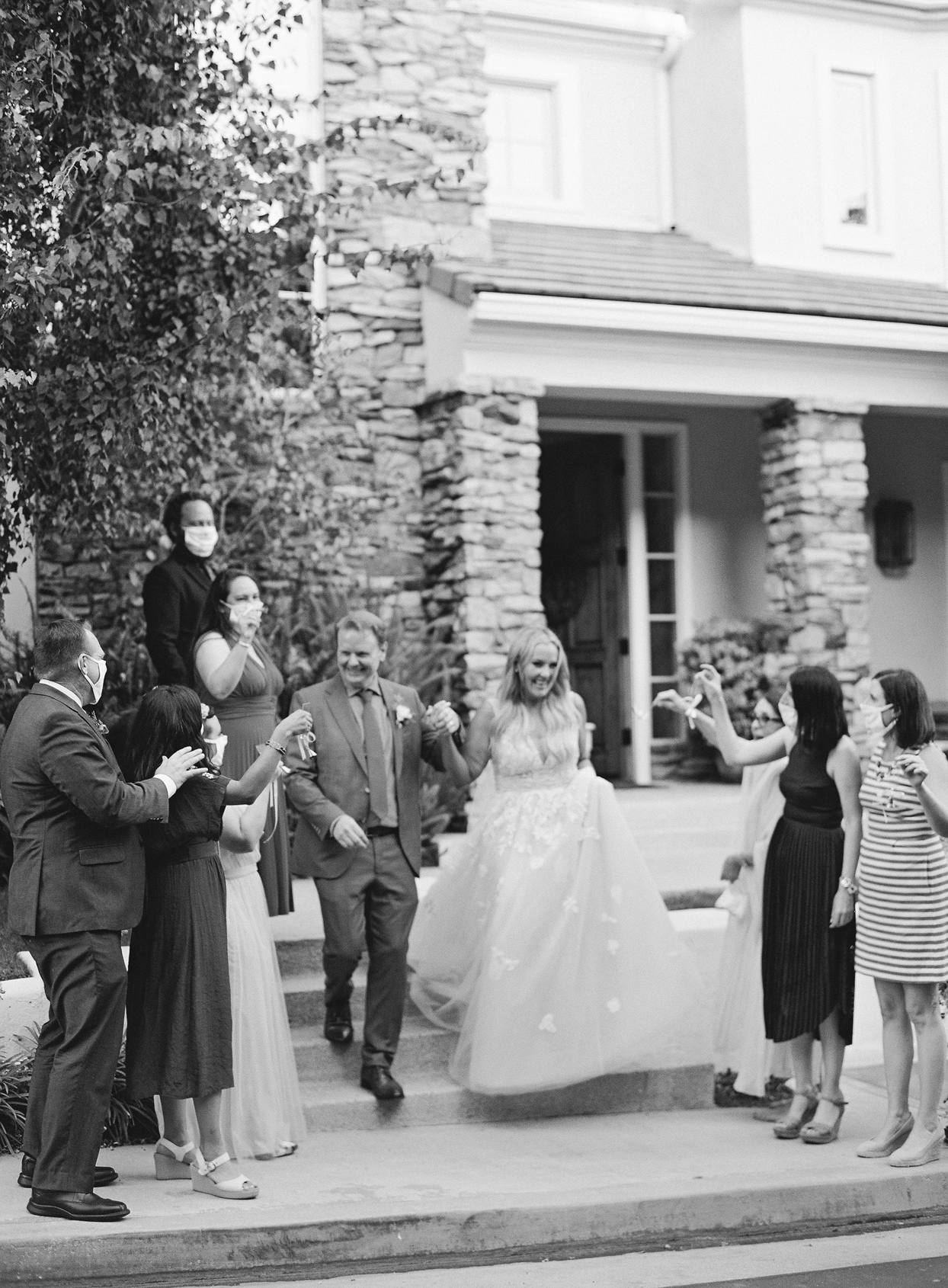 bride and groom walking down stairs surrounded by friends and family
