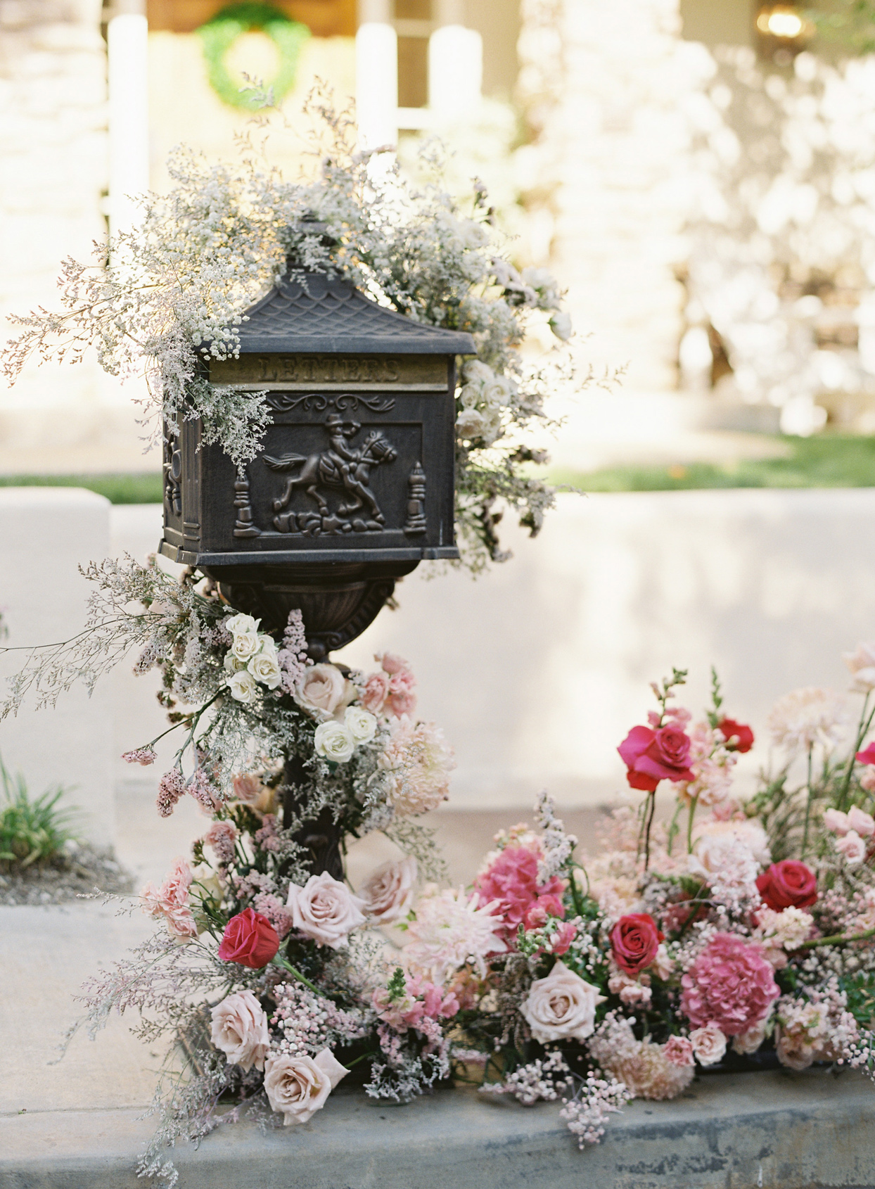 pink floral display on antique black mailbox
