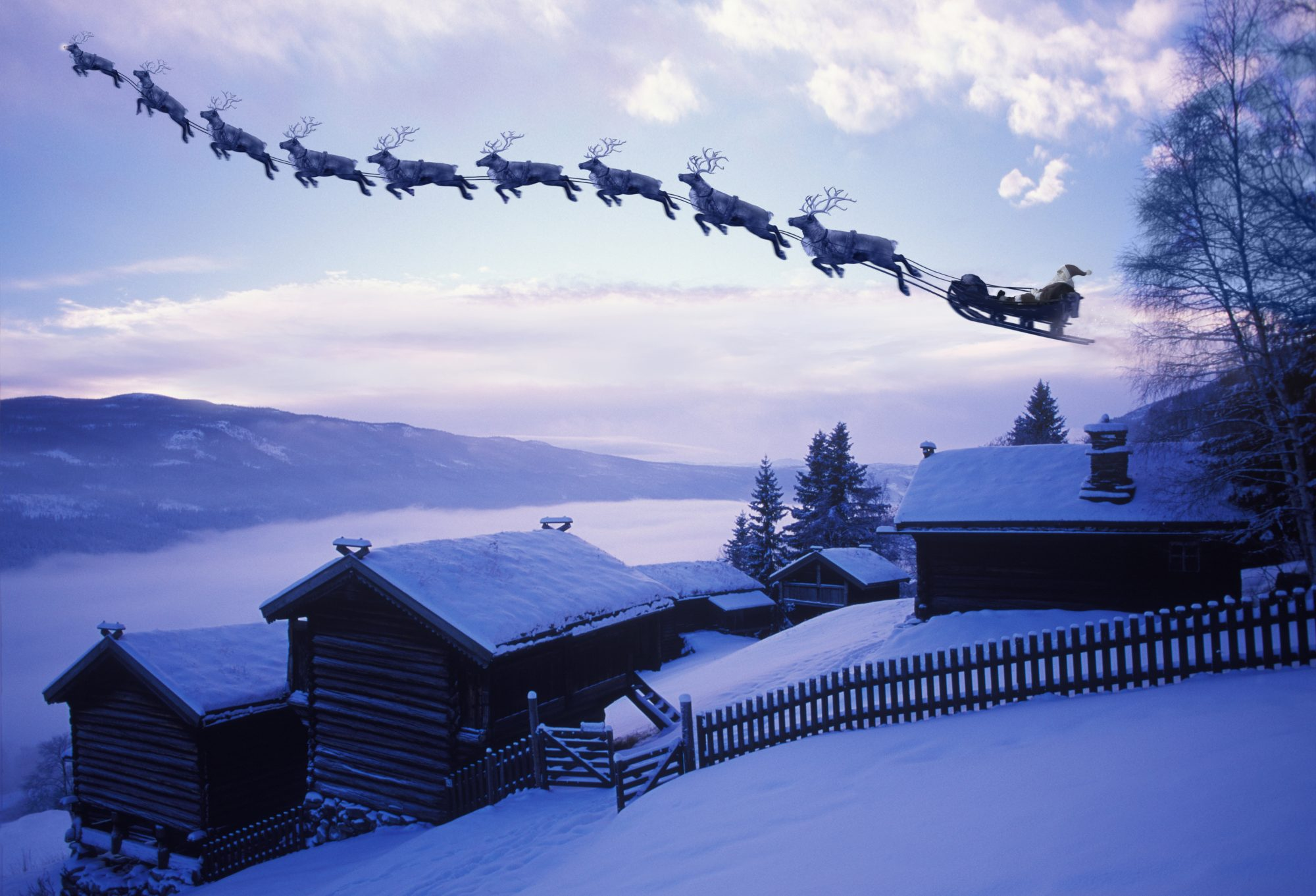 santa and reindeer flying over town in sleigh