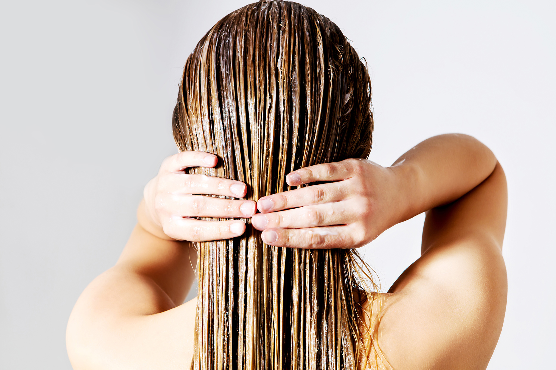 persons hands on long dirty blonde hair with conditioner