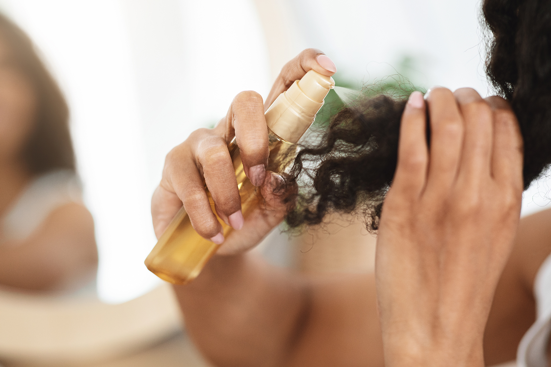 person spraying oil into curly dark brown hair