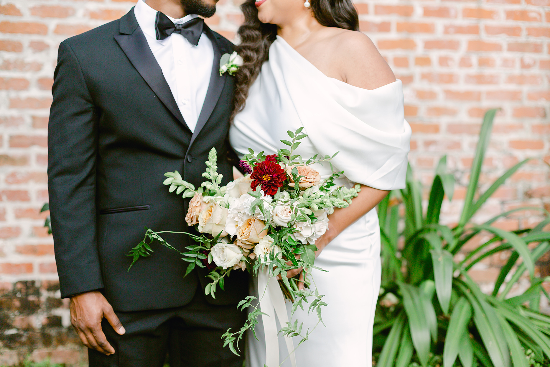 bride and groom with large floral wedding bouquet