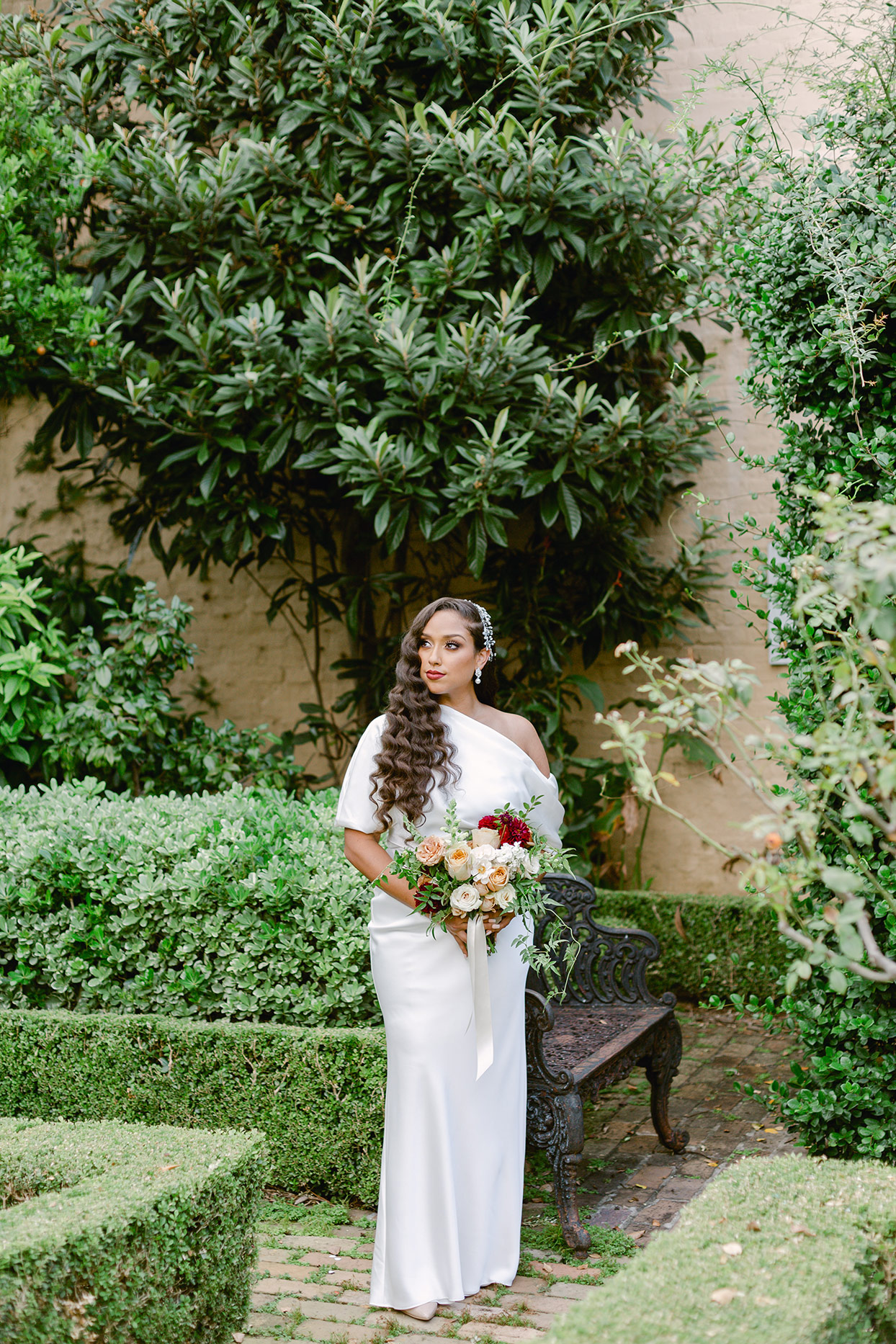 bride standing in garden holding bouquet wearing wedding dress