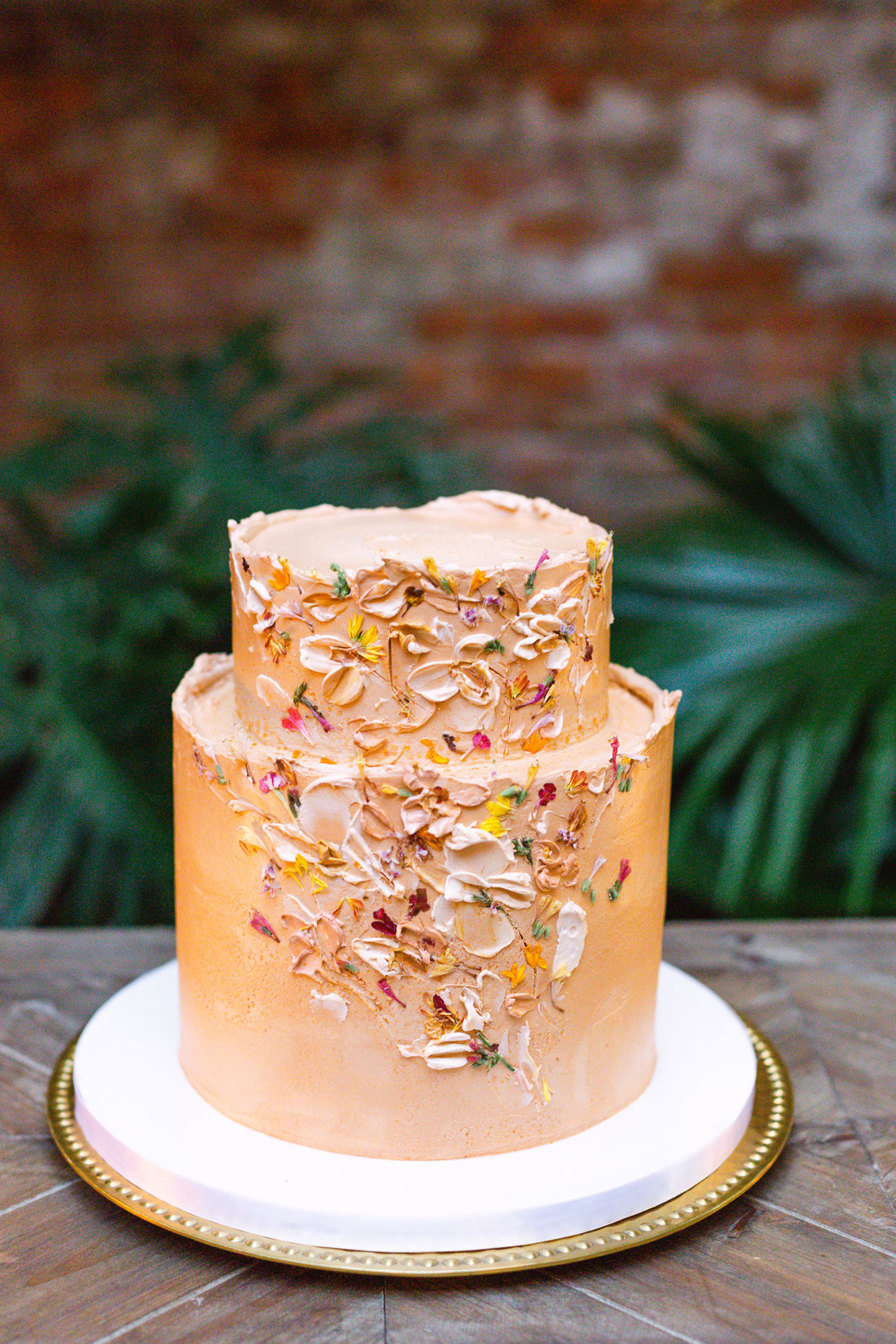 two tier orange frosted wedding cake on white tray