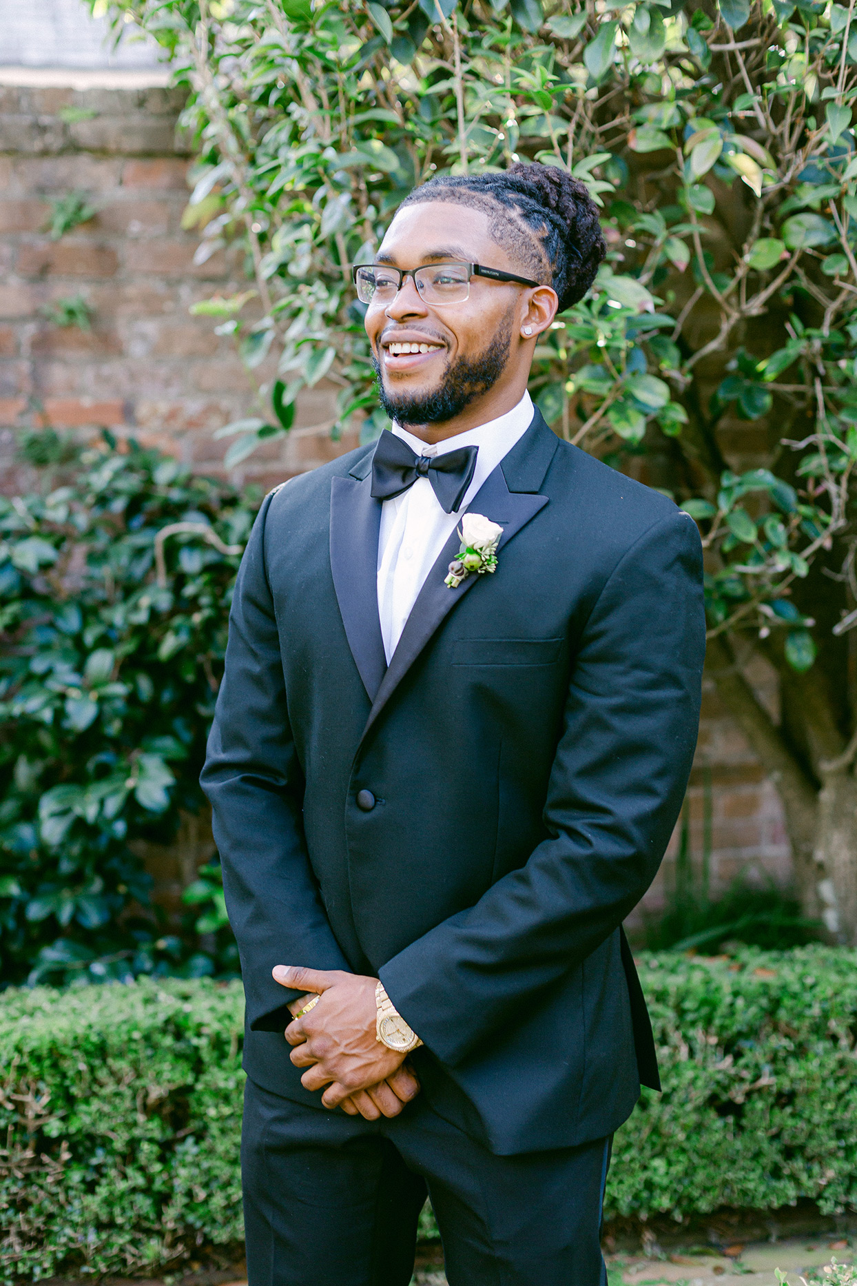 groom wearing black tuxedo smiling outside