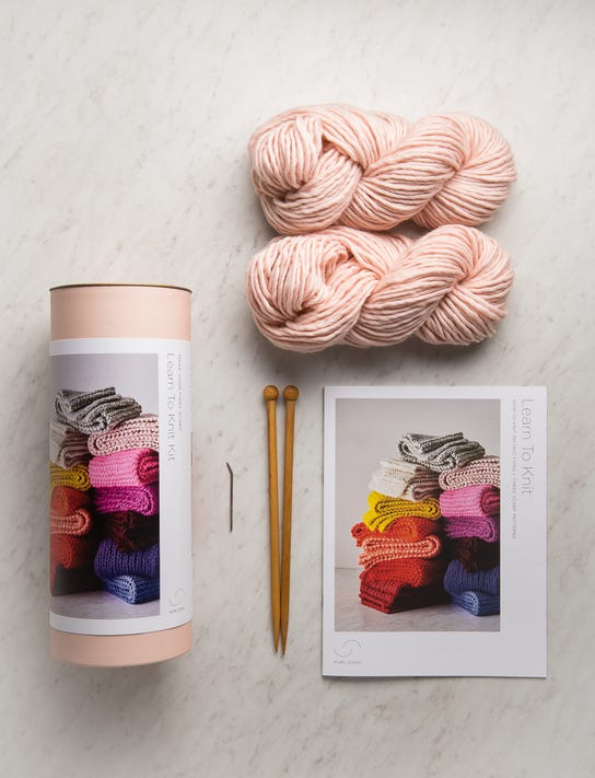Blush colored yarn with knitting needles