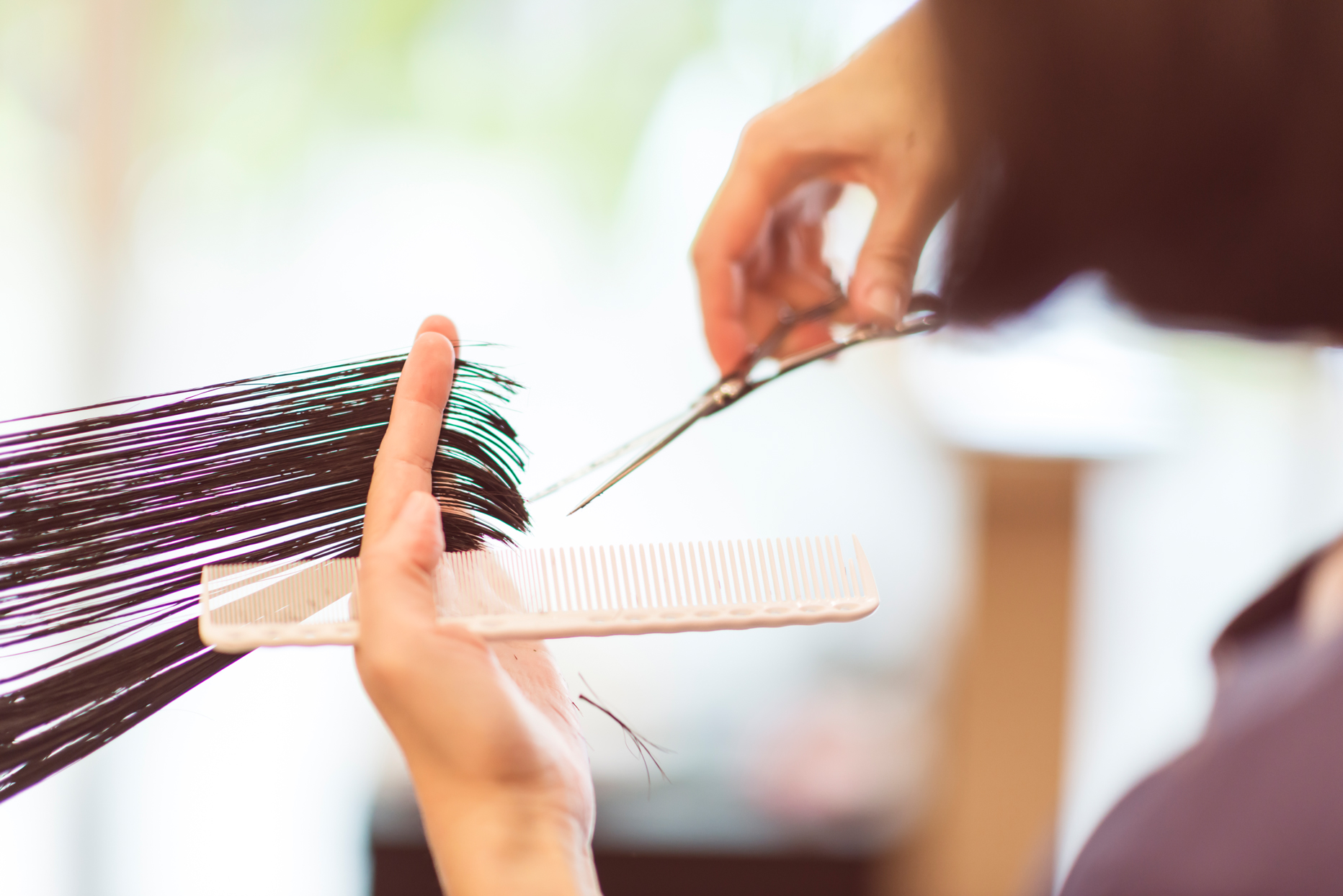 person cutting dark colored hair with scissors holding a comb