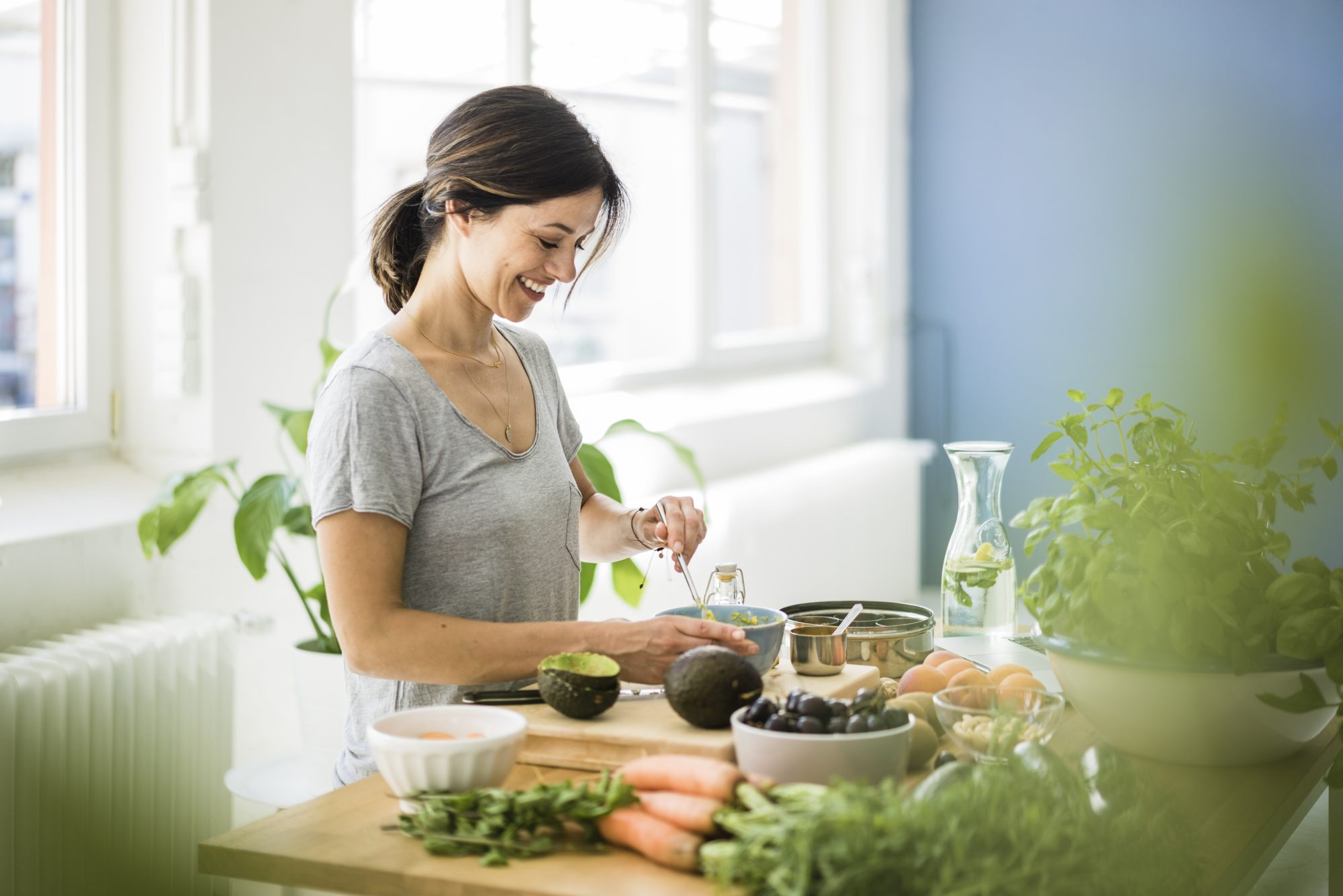 woman preparing avocado and vegetables in her kitchen